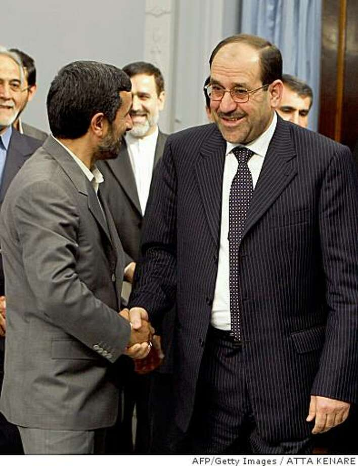 Iranian President Mahmoud Ahmadinejad (L) shakes hands with Iraqi Prime Minister Nuri al-Maliki (R) upon his arrival for a meeting in Tehran on June 8, 2008. Al-Maliki sought to reassure Iran over a planned security pact with Washington today, vowing Iraq would never be used as a platform to attack the Islamic republic. AFP PHOTO/ATTA KENARE (Photo credit should read ATTA KENARE/AFP/Getty Images) Photo: ATTA KENARE, AFP/Getty Images
