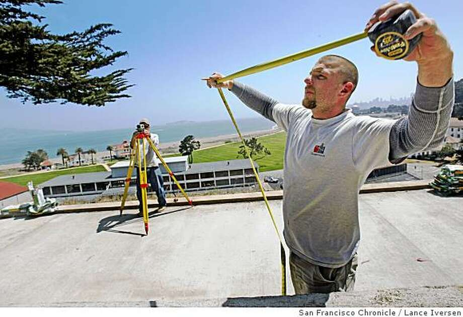 Juan Santoyo and Dillon Westbrook right, takes measurements as construction workers lay slabs of granite from China down as a walkway surface at the new overlook on Lincoln Blvd north of Doyle Drive. The overlook will offer spectacular views of the Presidio's Crissy Field; this in part is due to a $15 million grant from the Haas Foundation. Tuesday, May 6, 2008 in San Francisco, Calif. Photo By Lance Iversen / San Francisco Chronicle. Photo: Lance Iversen, San Francisco Chronicle