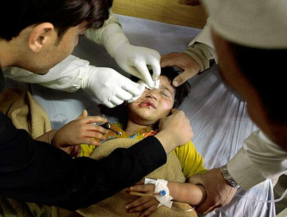 Pakistani medics treat a boy who was injured in a bomb blast at the the Inter Services Intelligence (ISI) building in Peshawar on November 13, 2009. At least seven people were killed by a huge blast that ripped through the local offices of Pakistan's premier intelligence agency in the northwestern city of Peshawar whilst a bombing at a police station in Bannu killed three policemen and wounded five others, a local police official said. TOPSHOTS    AFP PHOTO/ A MAJEED (Photo credit should read A Majeed/AFP/Getty Images) Photo: A Majeed, AFP/Getty Images