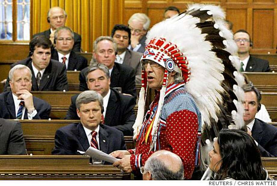Canada's Prime Minister Stephen Harper (bottom L) and other MP's listen as National Chief of the Assembly of First Nations Phil Fontaine (R) speaks in the House of Commons on Parliament Hill in Ottawa June 11, 2008. Canada, seeking to close one of the darkest chapters in its history, formally apologized on Wednesday for forcing 150,000 aboriginal children into grim residential schools, where many say they were abused.     REUTERS/Chris Wattie (CANADA) Photo: CHRIS WATTIE, REUTERS