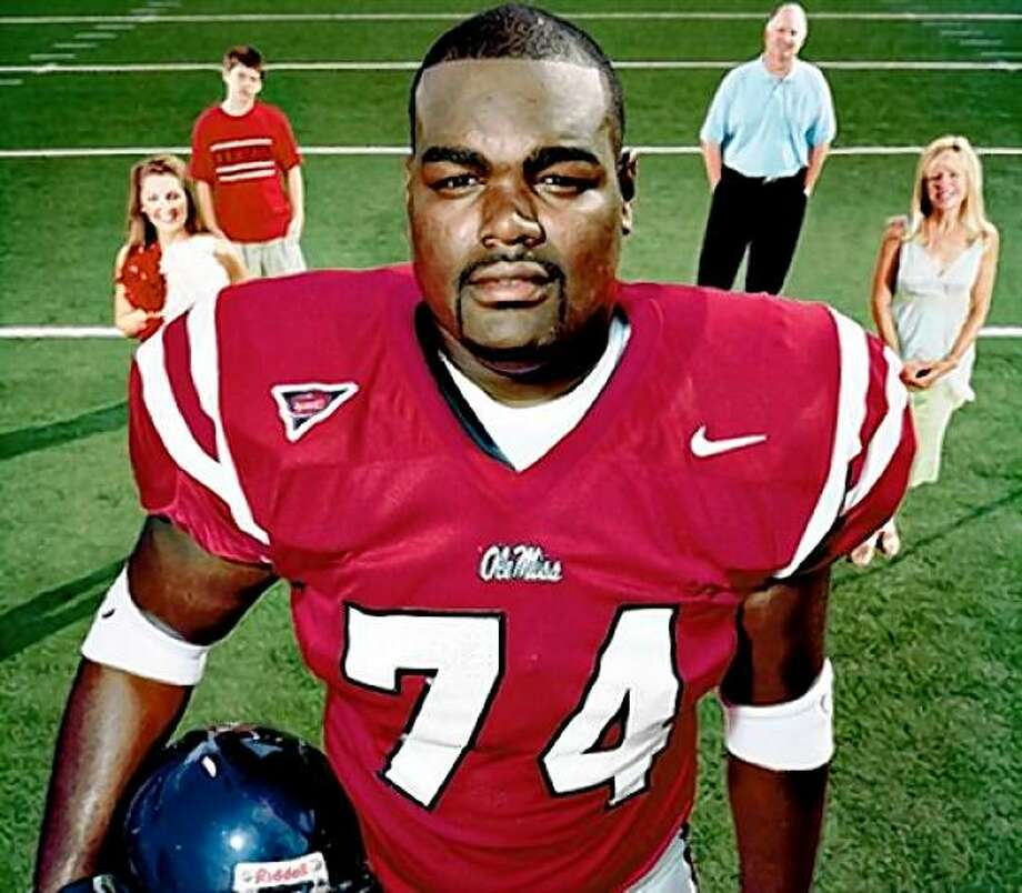 Michael Oher in his Ole Miss uniform with the Tuohy family in the background Photo: Googleimages