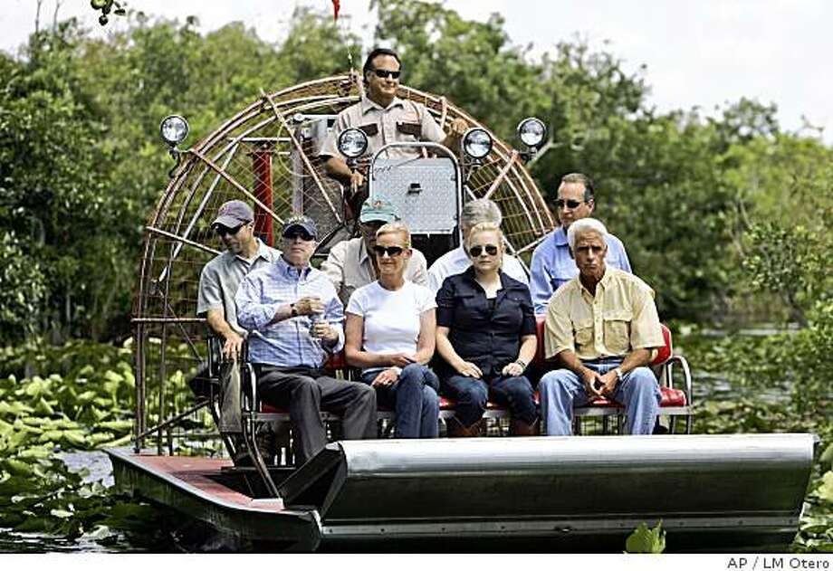 ** CORRECTS SPELLING TO MEGHAN ** Republican presidential candidate Sen. John McCain, R-Ariz., front row from left, takes a tour of the Florida Everglades with his wife Cindy, daughter Meghan, and Florida Gov. Charlie Crist near Miami, Fla., Friday, June 6, 2008. (AP Photo/LM Otero) Photo: LM Otero, AP