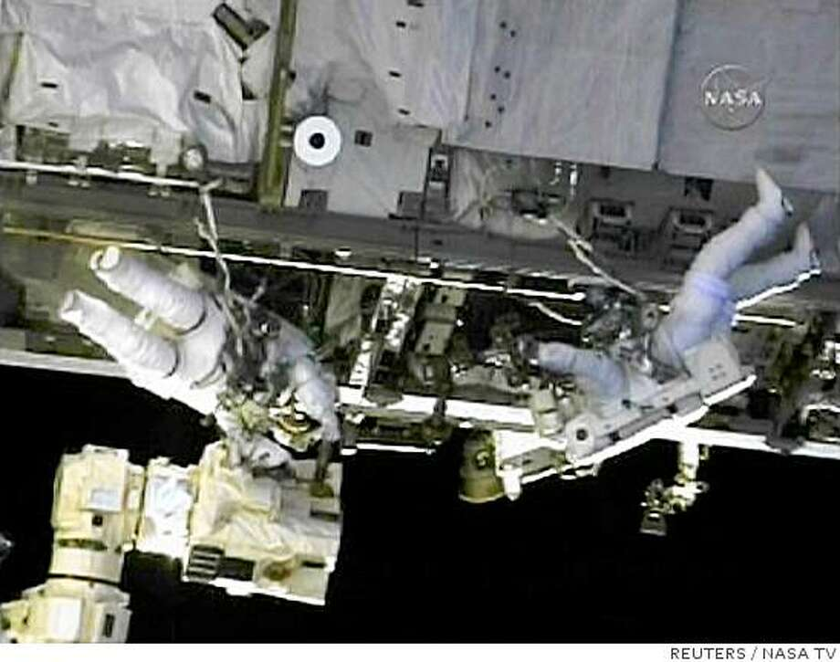 Mission Specialist Mike Fossum (L) helps Mission Specialist Ron Garan (R) with the foot restraint system on the 58-foot robot arm which Garan will ride during the spacewalk in this image from NASA TV June 8, 2008.   The spacewalking pair will replace a nitrogen tank assembly, install TV equipment and remove a thermal cover from Japan's new robotic arm during the planned 6 hour plus spacewalk. REUTERS/NASA TV  (UNITED STATES).  FOR EDITORIAL USE ONLY. NOT FOR SALE FOR MARKETING OR ADVERTISING CAMPAIGNS. Photo: NASA TV, REUTERS