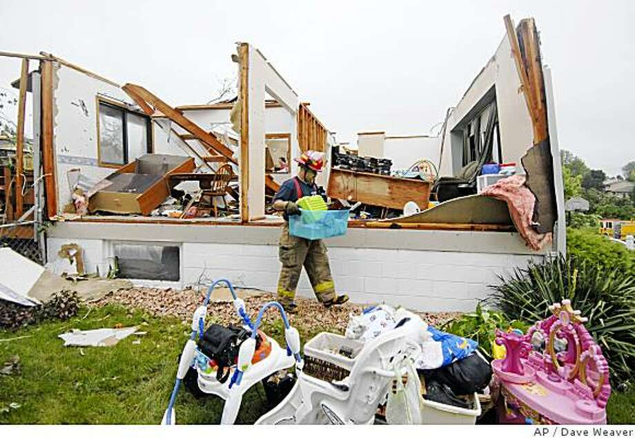 A firefighter carries belongings as resident Michelle Tanga is seen in the kitchen of her destroyed home, after a storm passed through the city early Sunday morning, June 8, 2008, causing damage to homes and downed trees and power lines in the Millard area in southwest Omaha, Neb.(AP Photo/Dave Weaver) Photo: Dave Weaver, AP