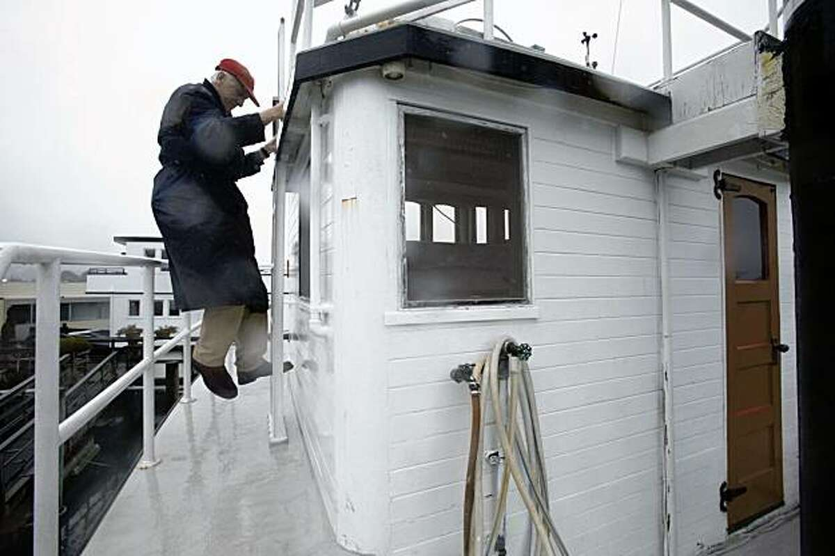 Brand climbs down from the top of his tugboat house.