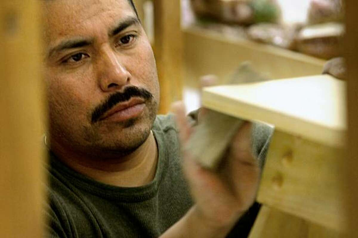 Juan Lopez puts the final touches of sanding a foot stool, Tuesday Nov. 10, 2009, in the Carpinteria Fina ( fine carpentry) class at Laney College in Oakland, Calif.
