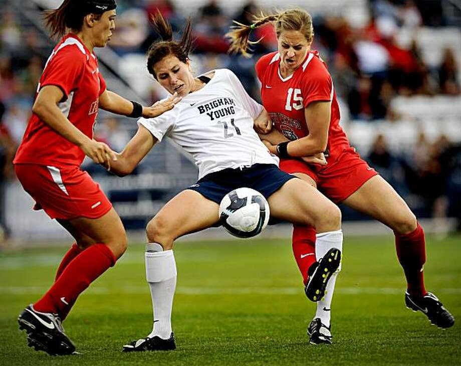 In this Nov. 5, 2009 photo, BYU forward Kassidy C. Shumway (21) is pulled to the ground by New Mexico defender Elizabeth Lambert (15) as she tries to maintain possession during the second half of an NCAA college soccer match in Provo, Utah. Lambert was suspended Friday, Nov. 6, 2009, for her infractions during the match. (AP Photo/Daily Herald, Patrick Smith) Photo: Patrick Smith, AP