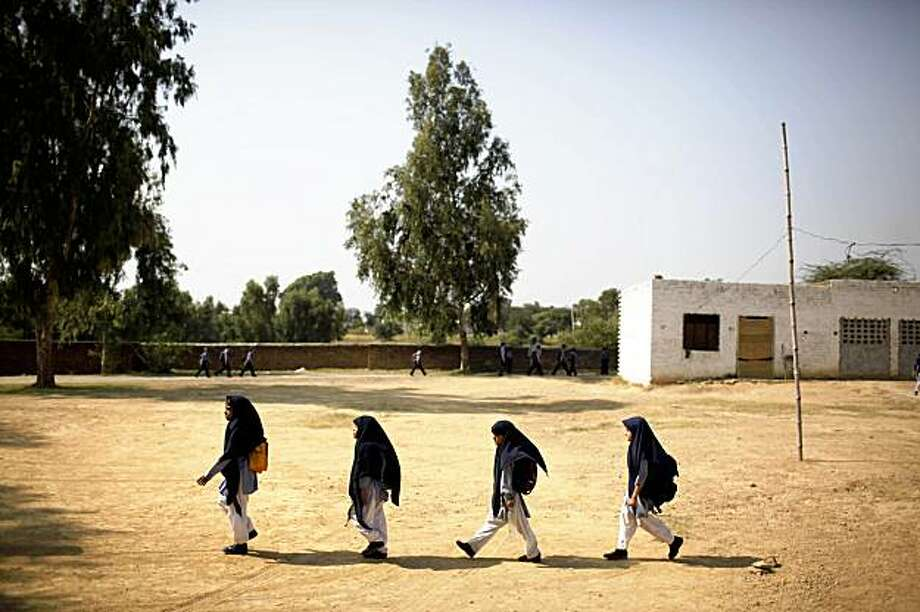 **ADVANCE FOR SUNDAY, NOV. 8** In this photo taken on Tuesday, Oct. 13, 2009, children leave their school after classes in Qutbal, Pakistan. Pakistan is seeing a surge in private schools, a trend some find hopeful in a country where the government education system is decrepit and the other alternative is the madrasas, religious schools which offer little education beyond memorizing the Quran and are seen as one source of Islamic militancy. (AP Photo/Alexandre Meneghini) Photo: Alexandre Meneghini, AP