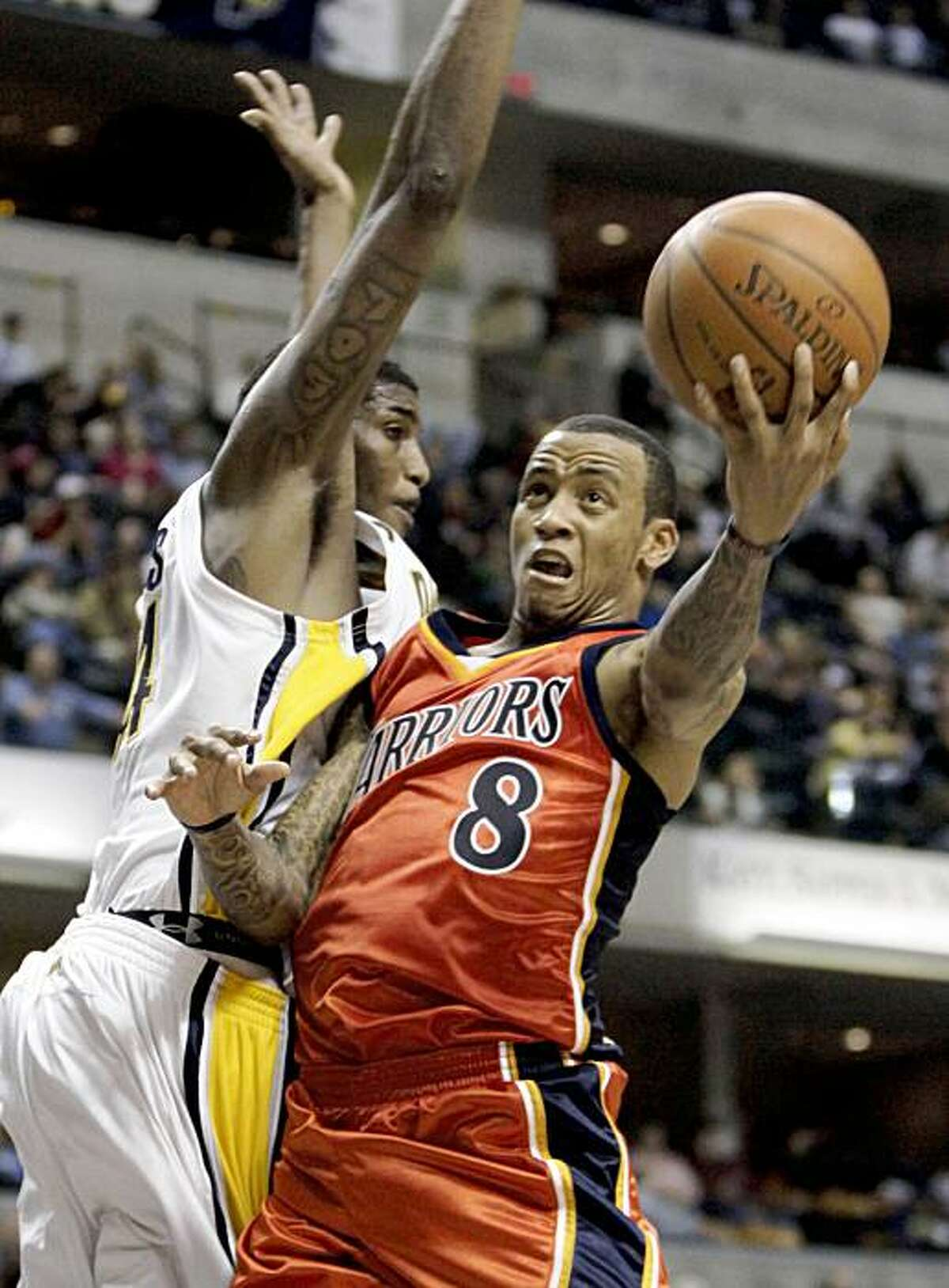 Golden State Warriors guard Monta Ellis, right, moves to the basket around Indiana Pacers center Solomon Jones during the second half of an NBA basketball game in Indianapolis, Wednesday, Nov. 11, 2009. The Pacers won 108-94. (AP Photo/AJ Mast)