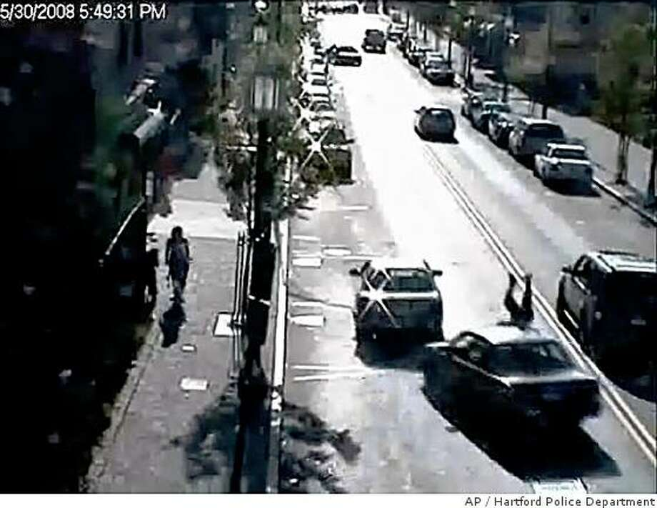 ** SECOND OF SIX IMAGES IN A SERIES ** This image taken from a surveillance video and provided by the Hartford Police Department shows a man, up-ended, in the lower right corner of the frame just as a car hits him, Friday May 30, 2008 in Hartford, Conn. The 78-year-old man was tossed like a rag doll by a hit-and-run driver, and car after car zoomed by as he laid motionless on the busy city street. The victim, Angel Arce Torres, was in critical condition in Hartford Hospital. Authorities say he is paralyzed. (AP Photo/Hartford Police Dept.) Photo: Hartford Police Department, AP