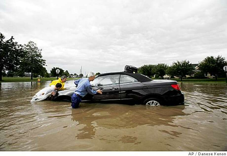 Henry Tsui , right, gets help from David Walke, and Kip McDonald  in pushing his rental car through the flood waters on McFarland Blvd Saturday, June 7, 2008, In Indianapolis.  Storms dumped as much as 10 inches of rain on soggy central Indiana on Saturday, threatening dams, inundating highways and sending the Coast Guard to rescue residents from swamped homes. (AP Photo/The Indianapolis Star, Danese Kenon) Photo: Danese Kenon, AP