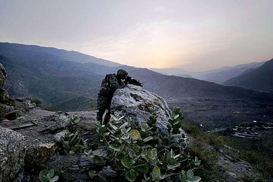 A U.S. soldier from the 2nd Battalion, 12th Infantry Regiment, 4th Brigade Combat Team, 4th Infantry Division takes an overwatch position on a mountain top as the sun rises in the Pech Valley of Afghanistan's Kunar province Saturday, Nov. 7, 2009. (AP Photo/David Guttenfelder) Photo: David Guttenfelder, AP