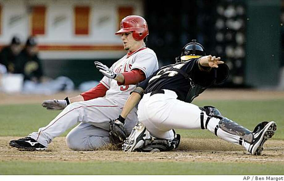 Los Angeles Angels' Brandon Wood, left, slides safe at home to score past the tag of Oakland Athletics catcher Kurt Suzuki during the seventh inning of a baseball game Saturday, June 7, 2008, in Oakland, Calif. Wood scored on a single by Maicer Izturis. (AP Photo/Ben Margot) Photo: Ben Margot, AP