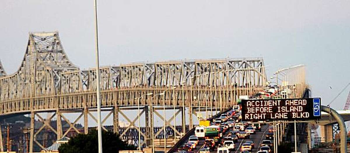 A sign warns motorists of an accident and the San Francisco-Oakland Bay Bridge on Monday, Nov. 9, 2009, in Oakland, Calif. A truck driver died earlier in the morning after he lost control on the bridge's temporary S-curve and crashed to the ground several hundred feet below. (AP Photo/Noah Berger)