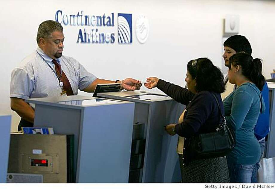 LOS ANGELES, CA - JUNE 05:  Continental Airlines agents help passengers with ticketing at Los Angeles International Airport (LAX) on June 5, 2008 n Los Angeles, California. The US air carrier has announced that it will cut 3,000 jobs, drop 67 of its less fuel-efficient jets, and reduce services to cope with skyrocketing fuel costs which the company describes as the worst crisis in the air travel industry since the travel slump that followed the September 11, 2001 terror attacks. With fuel prices about 75 percent higher than a year ago, Continental will dump its Boeing 737-300 aircraft fleet for new fuel-efficient Boeing 737-800s and 737-900ERs. The announcement comes a day after United Airlines said it is grounding 20 percent of its fleet, or about 100 jets, and eliminating up to 1,100 jobs because of the fuel cost crunch.  (Photo by David McNew/Getty Images) Photo: David McNew, Getty Images