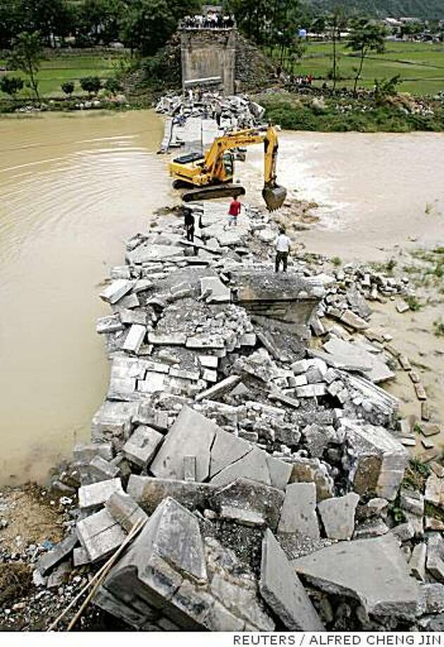 "An excavator removes the debris of a collapsed bridge which blocked a water channel in the town of Leigu in Beichuan County, Sichuan province June 7, 2008. Chinese troops on Saturday eased pressure on a swelling ""quake lake"" threatening hundreds of thousands of people, but a smaller lake burst its banks in a show of destructive force. REUTERS/Alfred Cheng Jin (CHINA) Photo: ALFRED CHENG JIN, REUTERS"