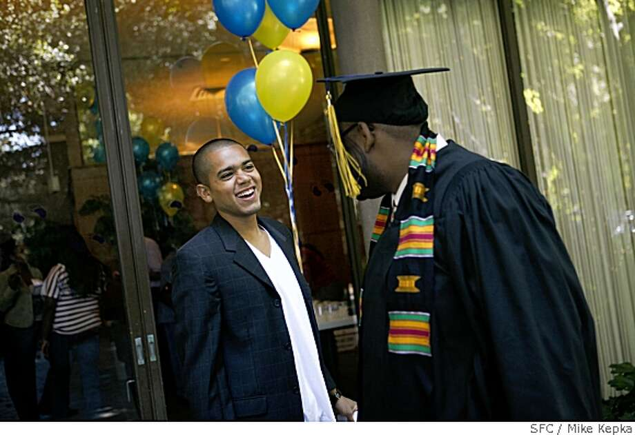 "David Cruz, 20, jokes around with friends during a small graduation ceremony at the UC Berkeley Alumni house  for students in the IDEAL scholarship program  on Wednesday May 21, 2008 in Berkeley, Calif.  ""This is my heart,"" Cruz said the added that there is no way he could have made it to college were not for the College Track and IDEAL scholarship programs.Photo by Mike Kepka / San Francisco Chronicle Photo: Mike Kepka, SFC"