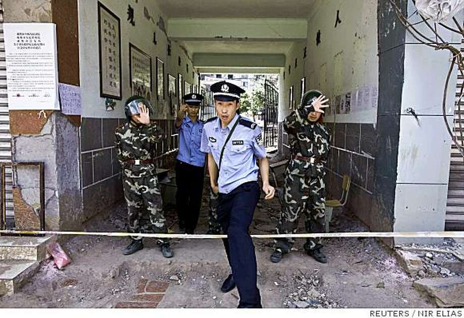 Police and soldiers react to being photographed as they guard the entrance to the earthquake-destroyed Xinjian primary school in Dujiangyan, Sichuan province June 4, 2008. At least two of the main reported schools that were open and welcomed foreign media coverage were closed today for media access with no clear reason given. Anguished Chinese parents said on Wednesday they will press ahead with complaints against officials they blamed for schools that toppled in a devastating earthquake, a day after police sought to silence one protest. REUTERS/Nir Elias (CHINA) Photo: NIR ELIAS, REUTERS