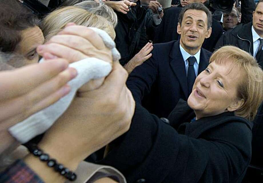 """French President Nicolas Sarkozy, top right, and German Chancellor Angela Merkel shakes hands to onlookers after Armistice Day ceremonies Wednesday Nov. 11, 2009 in Paris. France is commemorating the end of World War I hand-in-hand with the country vanquished in the so-called """"great war"""" as German Chancellor Merkel joins President Sarkozy to remember the fallen and to celebrate peace. (AP Photo/Philippe Wojazer; Pool) Photo: Philippe Wojazer, AP"""
