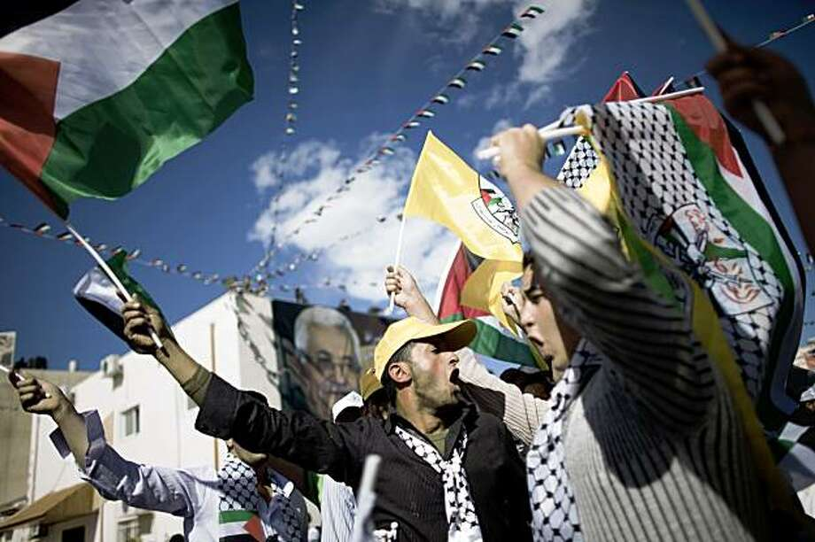 Palestinians shout slogans and wave their national flag as they attend a rally commemorating the fifth anniversary of late Palestinian leader Yasser Arafat's death in the West Bank city of in Ramallah on November 11, 2009. The fifth anniversary of Arafat's death finds Palestinians more divided than ever and his successor Abbas pondering resignation because of stalled US-led peace efforts that have failed to bring about an independent Palestinian state. AFP PHOTO/MARCO LONGARI (Photo credit should read MARCO LONGARI/AFP/Getty Images) Photo: Marco Longari, AFP/Getty Images