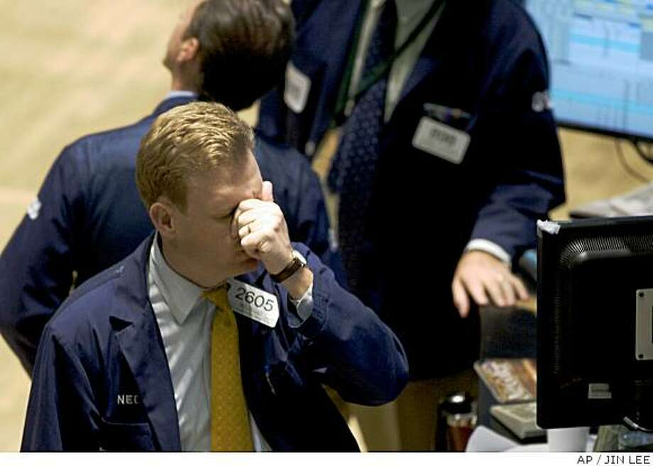 Ned Zeller rubs his eyes while working on the floor of the New York Stock Exchange on Friday, June 6, 2008 in New York. Stocks plunged Friday, sending the Dow Jones industrials down nearly 400 points, after oil prices shot up by more than $11 a barrel and neared $140 a barrel _ and wiped out investors' recent optimism about the economy in the process. (AP Photo/Jin Lee) Photo: JIN LEE, AP