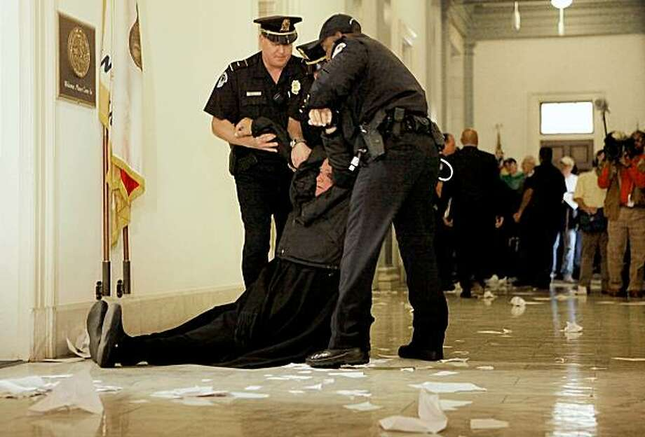 WASHINGTON - NOVEMBER 05:  Fr. Norman Weslin (R) of Omaha, Nebraska, is dragged by U.S. Capitol Police after refusing to leave Speaker of the House Nancy Pelosi's (D-CA) office while demonstrating against the health care reform bill at the Cannon House Office Building November 5, 2009 in Washington, DC. The protesters were voicing their opposition to Congress' health care reform legislation, saying it supports government funding of abortion.  (Photo by Chip Somodevilla/Getty Images) Photo: Chip Somodevilla, Getty Images