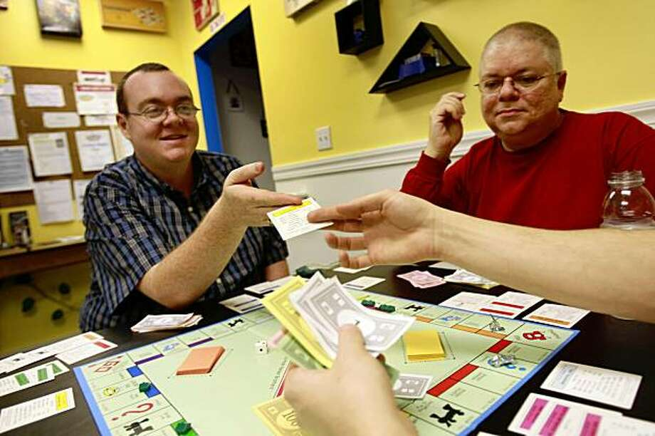 "Robbie Miller (left) of San Francisco hands over a property purchased by Erik Mantsch (far right hands only), owner ""Just Awesome"" during Monday's Monopoly Night as Fred Condo (right in red shirt), of San Francisco, looks on   at ""Just Awesome"" in San Francisco,Calif. on Monday, June 7, 2009. Photo: Lea Suzuki, The Chronicle"