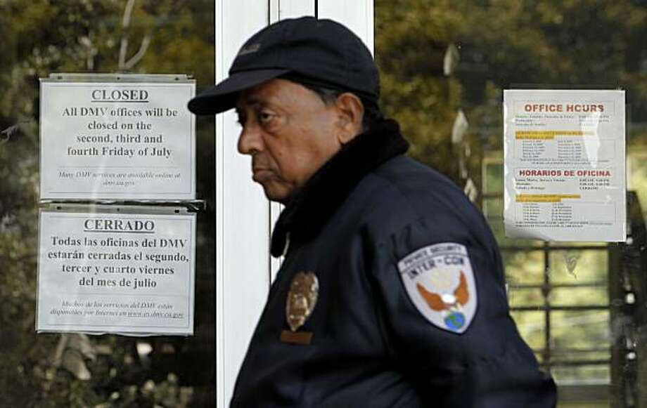 FILE - In this Friday, July 19, 2009 file photo, security guard Suresh Sonpaki walks in front of the doors of a closed Department of Motor Vehicles (DMV) office in San Francisco. California's ongoing fiscal crisis has attracted national attention, but a study warns that nine other states are barreling toward similar economic disaster. (AP Photo/Jeff Chiu) Photo: Jeff Chiu, Associated Press