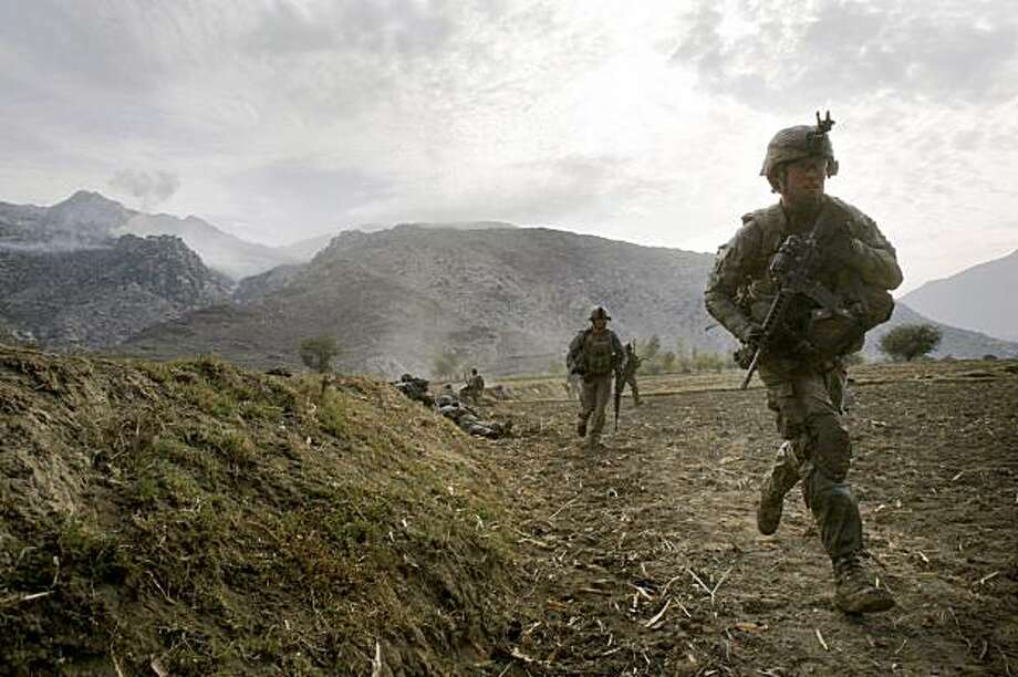 In this Tuesday, Nov. 3, 2009 photo, U.S. soldiers from the 2nd Battalion, 12th Infantry Regiment, 4th Brigade Combat Team, 4th Infantry Division pull back from a farm field where they took cover from a Taliban attack in the Pech Valley of Afghanistan's Kunar province. (AP Photo/David Guttenfelder) Photo: David Guttenfelder, AP