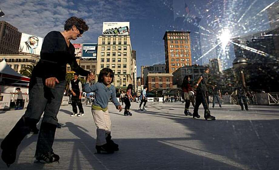 Catherine Teare and her daughter Sadie Leahy-Teare, 4 of Piedmont,  navigate their way around the Holiday Ice Rink in Union Square which opened today on Wednesday November 11, 2009 in San Francisco, Calif., for the Christmas season. The sun reflects off the plexi glass that circles the rink. Photo: Michael Macor, The Chronicle