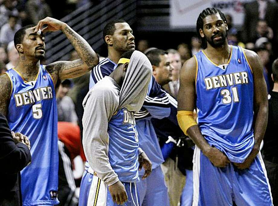 Denver Nuggets players, from left, J.R. Smith, Ty Lawson, with shirt over his face, and Nene, from Brazil, wait for officials to rule on a shot by Chicago Bulls center Brad Miller at the end of an NBA basketball game Tuesday, Nov. 10, 2009, in Chicago. After a video view, officials ruled time had expired before Miller's shot, and the Nuggets won 90-89.  (AP Photo/Charles Rex Arbogast) Photo: Charles Rex Arbogast, AP