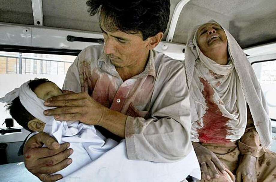 A Pakistani holds his baby girl, who was killed in a suicide bombing, as her grandmother mourns inside a van at a local hospital in Peshawar, Pakistan on Sunday, Nov. 8, 2009. A suicide bomber apparently targeting an anti-Taliban mayor struck a crowded market Sunday in northwest Pakistan, killing the mayor, police said. (AP Photo/Mohammad Iqbal) Photo: Mohammad Iqbal, AP