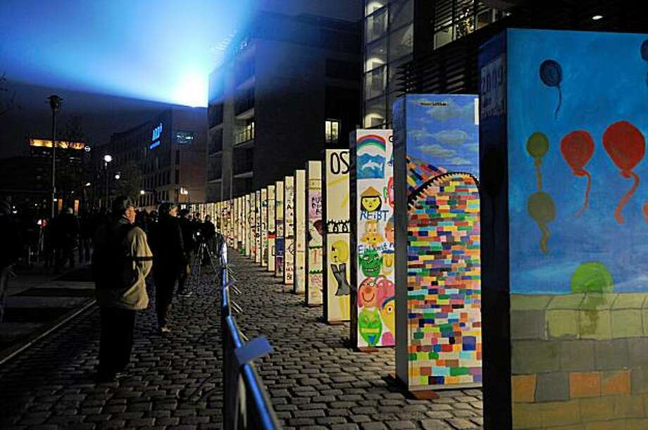 Peopl look at the individually painted dominos along the former route of the wall in Berlin, on November 8, 2009, as part of the celebrations of the 20th anniversary of the fall of the Berlin Wall on November 9, 2009. Some 1,000 giant dominos, many of them decorated by schoolchildren, will be toppled during the official ceremony.  AFP PHOTO   ERIC FEFERBERG (Photo credit should read ERIC FEFERBERG/AFP/Getty Images) Photo: Eric Feferberg, AFP/Getty Images
