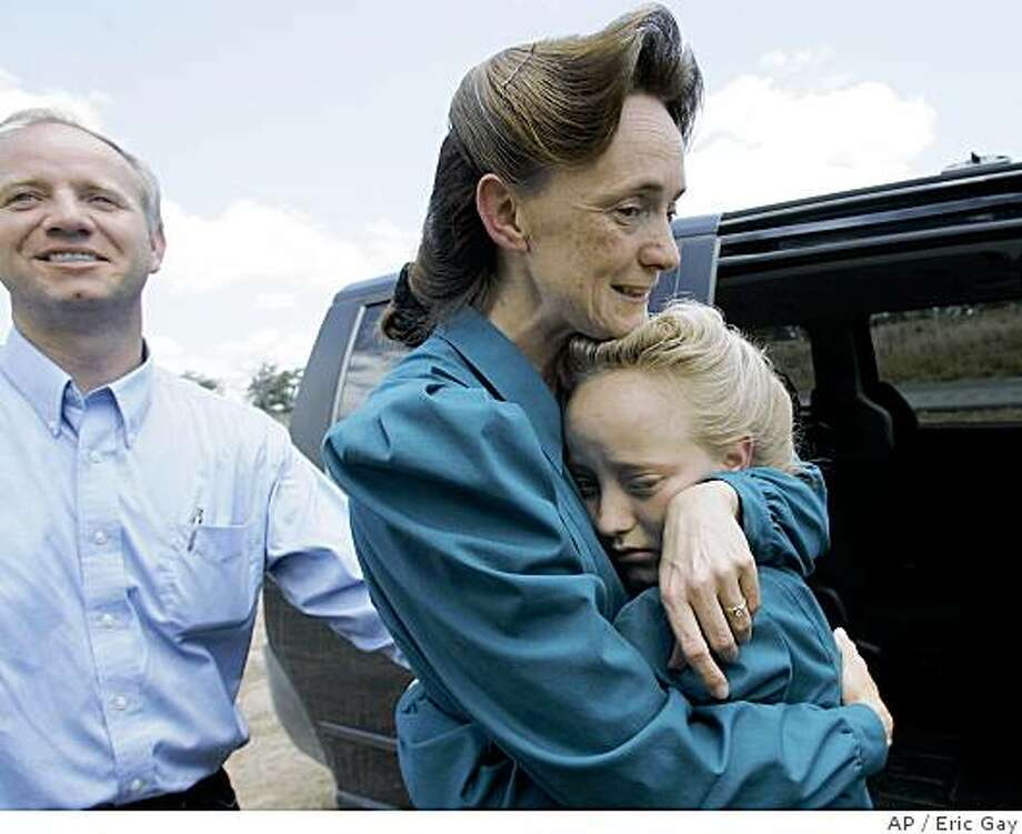** CAPTION CORRECTION CORRECTS SPELLING OF LULING, NOT LULLING ** James, left, and Nancy Dockstader, center, members of the Fundamentalist Church of Jesus Christ of Latter Day Saints, greet their daughter Amy, 9, after they were reunited at the Baptist Children's Home Ministries Youth Camp near Luling, Texas,  Monday, June 2, 2008. (AP Photo/Eric Gay) Photo: Eric Gay, AP