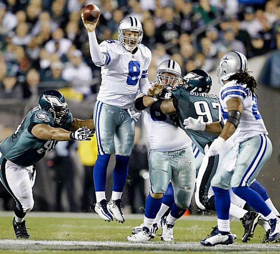 Dallas Cowboys quarterback Tony Romo, center, passes to running back Marion Barber, right, as Philadelphia Eagles defensive tackle Mike Patterson, left, reaches for Romo during the first half of an NFL football game Sunday, Nov. 8, 2009, in Philadelphia. (AP Photo/Matt Slocum) Photo: Matt Slocum, AP