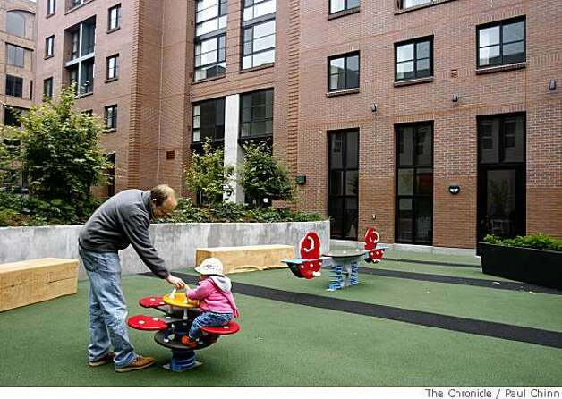 Project architect Alan Christ plays with his 15-month-old daughter Meredith in the playground at the Broadway Family Apartments in San Francisco, Calif., on Saturday, May 31, 2008. The brand-new 80-unit low income housing development was built near the site of the old Embarcadero Freeway off-ramp. Photo: Paul Chinn, The Chronicle