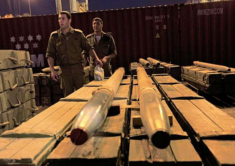 Israeli soldiers unpack rockets seized by Israeli authorities on a ship near Cyprus, and presented in the port of the Israeli city of Ashdod, Wednesday, Nov. 4, 2009. Israeli commandos seized a ship Wednesday that defense officials said was carrying hundreds of tons of weapons from Iran bound for Lebanon's Hezbollah guerrillas, the largest arms shipment Israel has ever commandeered.(AP Photo/Tsafrir Abayov ) Photo: Tsafrir Abayov, AP