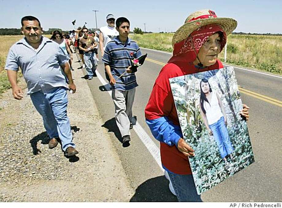 Josefina Flores, right,  carries a photograph of Maria Isabel Vasques Jimenez, an undocumented farm worker who collapsed and died in a vineyard last month because her employer denied her water, during a march to protest her death, near Thornton, Calif.,  Monday, June 2, 2008.  Relatives and farmworker advocates are calling the death of the young, pregnant field worker a symbol of inhuman conditions at dozens of California's farms.  Seen in  center, carrying flowers is Florentino Bautista, Maria Jimenez's fiance.(AP Photo/Rich Pedroncelli) Photo: Rich Pedroncelli, AP