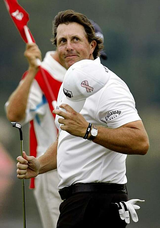 American Phil Mickelson takes off his cap to greet spectators at the 18th green after the third round of the 2009 HSBC Champions golf tournament at Shanghai Sheshan International Golf Club Saturday, Nov. 7, 2009 in Shanghai, China.  Mickelson shot a 67 and took the third-day lead with 14-under 202.(AP Photo/Eugene Hoshiko) Photo: Eugene Hoshiko, AP