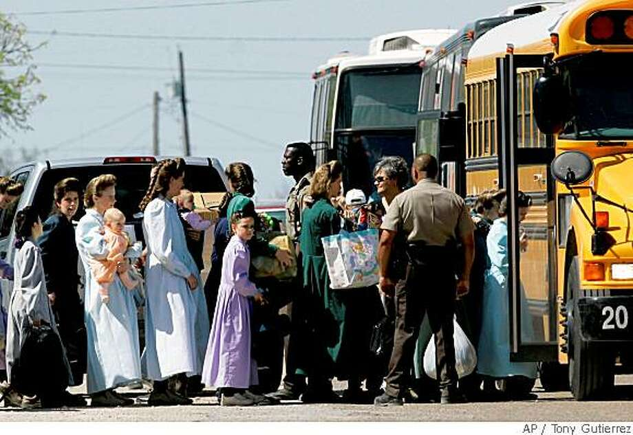 Members of the Fundamentalist Church of Jesus Christ of Latter Day Saints walk toward a waiting charter bus as Schleicher County Sheriffs deputies help provide security, Sunday, April 6, 2008, in Eldorado, Texas. An Austin, Texas, appeals court ruled that the state had no cause to take their children. On Friday, May 30, Texas child welfare officials agreed the parents could take their children back. (AP Photo/Tony Gutierrez) Photo: Tony Gutierrez, AP