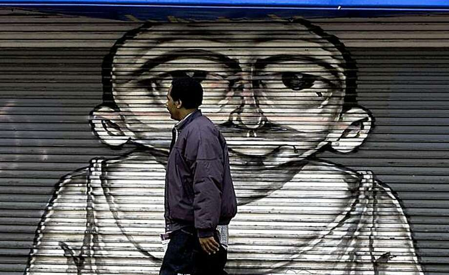 A Pedestrian walks in front of a closed fashion house on Market Street between 6th & 7th streets. The San Francisco Redevelopment Committee is drafting a plans to revive the blighted mid Market Street area.  By LANCE IVERSEN/SAN FRANCISCO CHRONICLE Photo: Lance Iversen, The Chronicle