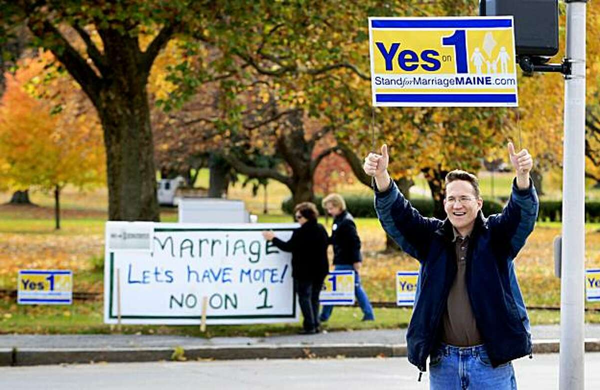 Joseph Skinner, who declined to say where he is from, holds up a Yes on 1 sign to passing motorists while in the background supporters of same-sex marriage Ann DiMella and Suzanne Blackburn, of Portland, put up a No on 1 sign at Deering Oaks Park, Tuesday, Nov. 3, 2009, in Portland, Maine. Voters will decide Question 1, the proposal to rescind the Legislature's approval of same-sex marriage.(AP Photo/Robert F. Bukaty)
