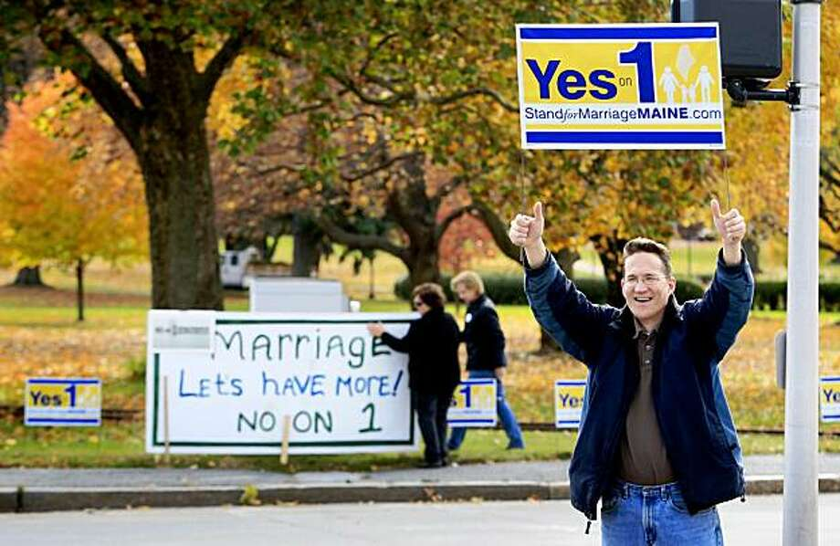 Joseph Skinner, who declined to say where he is from, holds up a Yes on 1 sign to passing motorists while in the background supporters of same-sex marriage Ann DiMella and Suzanne Blackburn, of Portland, put up a No on 1 sign at Deering Oaks Park, Tuesday, Nov. 3, 2009, in Portland, Maine. Voters will decide Question 1, the proposal to rescind the Legislature's approval of same-sex marriage.(AP Photo/Robert F. Bukaty) Photo: Robert F. Bukaty, AP