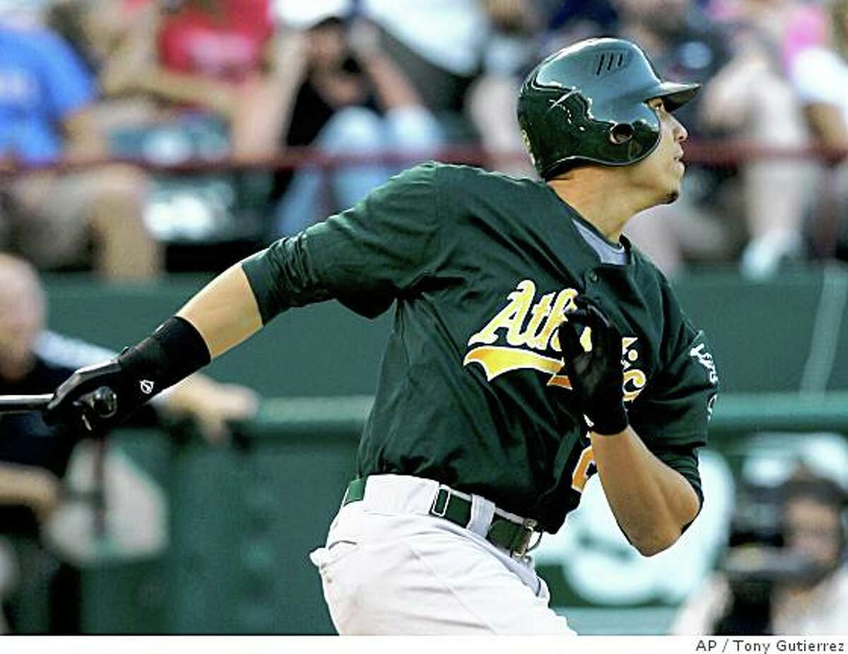 Oakland Athletics' Carlos Gonzalez follows through on a double to left in his first Major League at-bat in the third inning of a baseball game off a pitch from Texas Rangers' Kevin Millwood, Friday, May 30, 2008, in Arlington, Texas. Associated Press photo by Tony Gutierrez