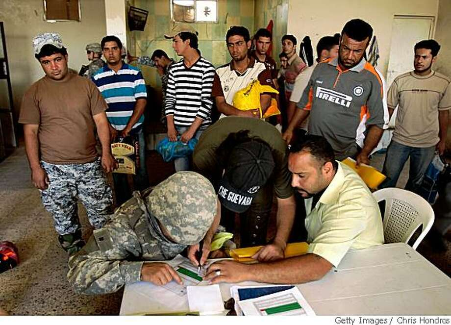 BAGHDAD, IRAQ - MAY 11:  A translator for the 3-89 Cavalry Regiment of the 10th Mountain Division (L) processes members of the Sons of Iraq, a local U.S. funded security group, as they line up to be paid May 11, 2008 in the Rusafa neighborhood of east Baghdad, Iraq. Army officials plan to disband the group, saying that security issues in the area will be handled by the Iraqi government police and army forces. Rusafa has largely been spared the violence that has plagued other east Baghdad Shiite neighborhoods recently. The 10th Mountain troops in Rusafa are concentrating on continuing to gather intelligence while building relationships with local Iraqi police and army forces.  (Photo by Chris Hondros/Getty Images) Photo: Getty Images