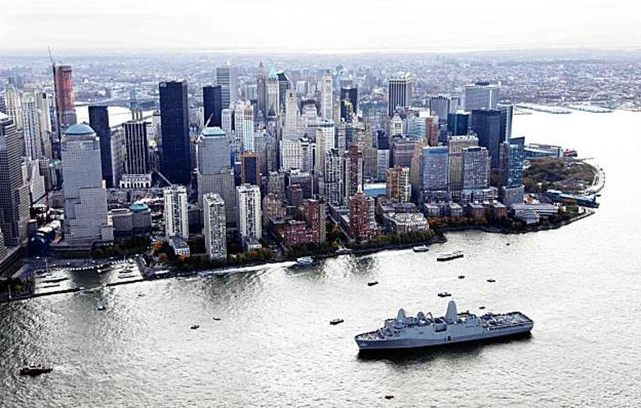 The new Navy assault ship USS New York, built with World Trade Center steel, passes lower Manhattan as it arrives Monday, Nov. 2, 2009 in New York. The World Trade Center construction site is at left. (AP Photo/Mark Lennihan) Photo: Mark Lennihan, AP