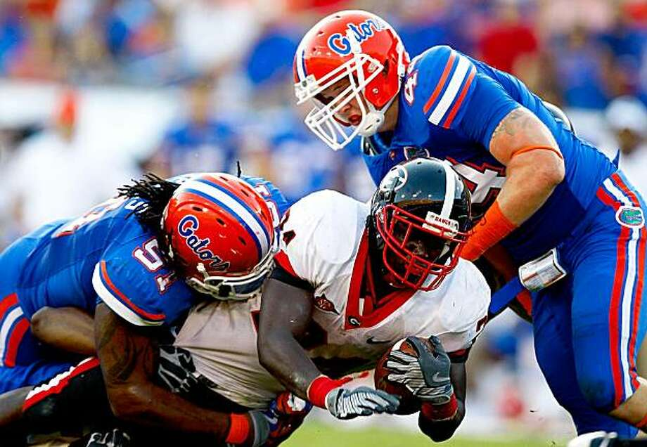 JACKSONVILLE, FL - OCTOBER 31:  Brandon Spikes #51 and Duke Lemmens #44 of the Florida Gators tackle Washaun Ealey #24 of the Georgia Bulldogs at Jacksonville Municipal Stadium on October 31, 2009 in Jacksonville, Florida.  (Photo by Kevin C. Cox/Getty Images) Photo: Kevin C. Cox, Getty Images