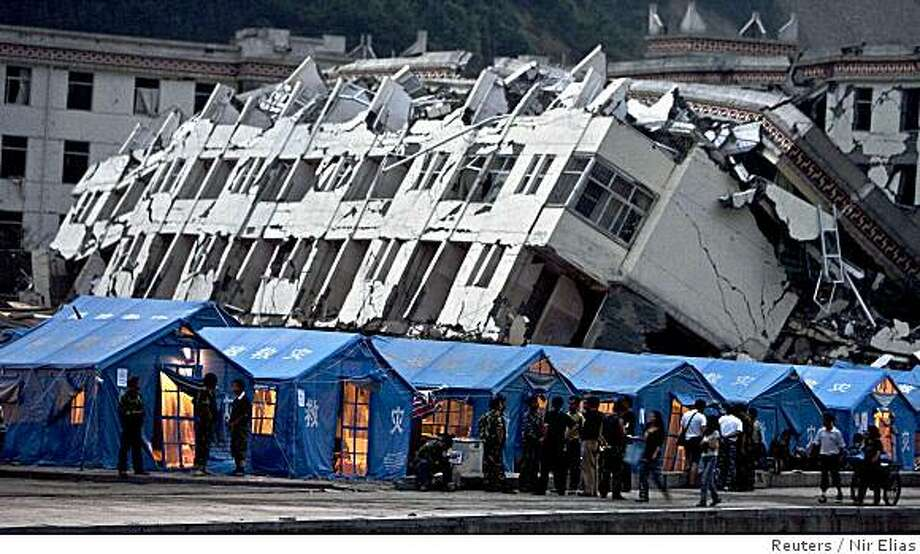 Survivors of the May 12 earthquake stand outside their tents in front of the badly damaged middle school of Yingxiu, in Sichuan province  on Monday, June 2, 2008.   Reuters photo by Nir Elias Photo: Nir Elias, Reuters