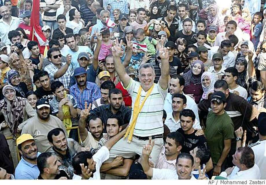 Nasim Nisr, a Lebanese man convicted in Israel of spying, gestures, as people carry him on their shoulders in his home southern village of Bazouriyeh, Lebanon, Sunday, June 1, 2008. Nisr was born to a Jewish Lebanese mother and a Shiite father. He was released Sunday after spending six years in prison in Israel on charges of spying for Hezbollah. (AP Photo/Mohammed Zaatari) Photo: Mohammed Zaatari, AP