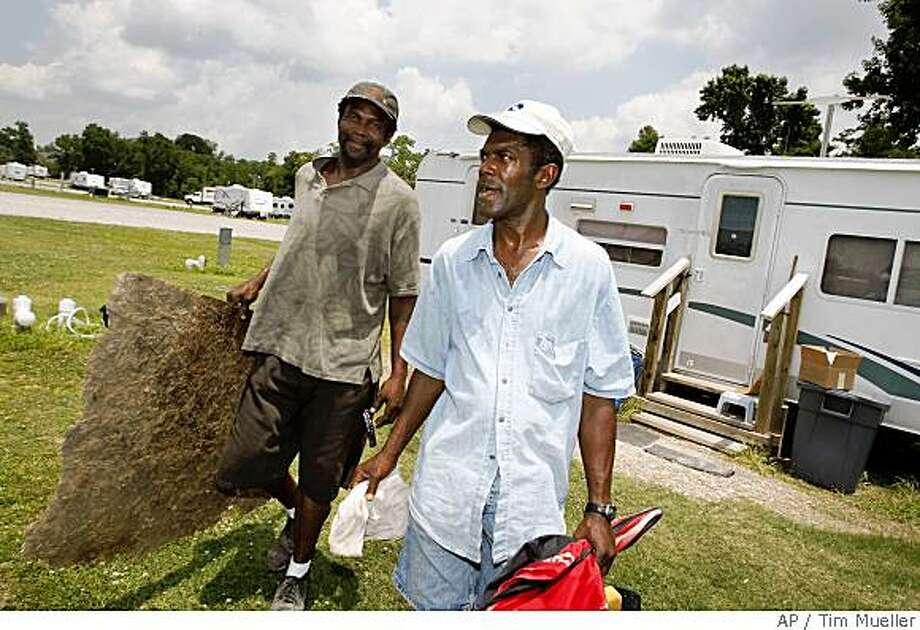 Renaissance Village trailer park resident Derrick Williams, right, and his friend Larry Jackson hauls items to the dumpster on  Saturday, May 31, 2008 as Williams prepares to move from the FEMA site in Baker, La. to a nearby apartment.  FEMA is trying to close its last six trailer parks in Louisiana by Sunday, June 1, 2008. (AP Photo/Tim Mueller) Photo: Tim Mueller, AP